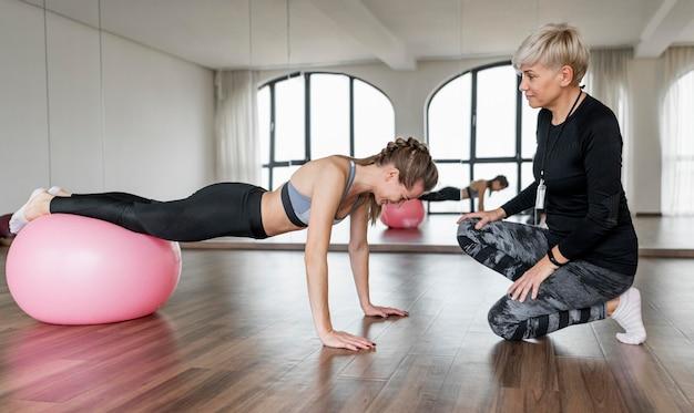 Vrouwelijke persoonlijke trainer en cliënt die geschiktheidsbal gebruiken