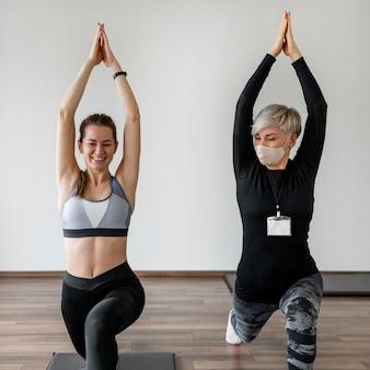 Vrouwelijke persoonlijke trainer en cliënt die yogaoefening doen
