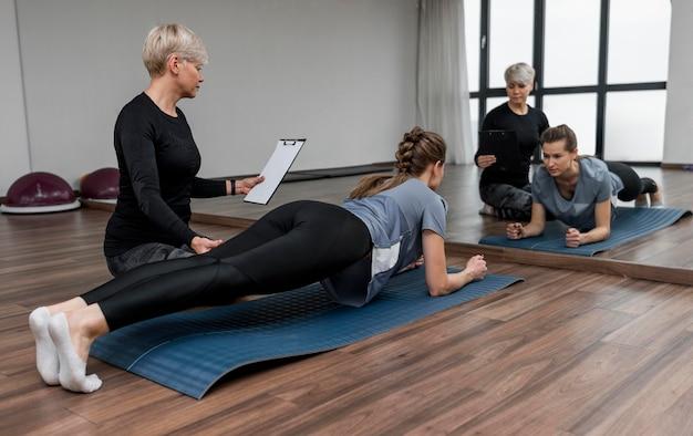 Vrouwelijke persoonlijke trainer en haar cliënt die plank doen