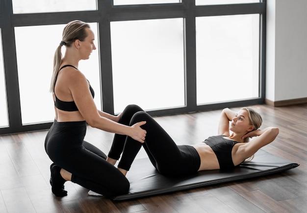 Vrouwelijke persoonlijke trainer en haar cliënt die push-ups doen
