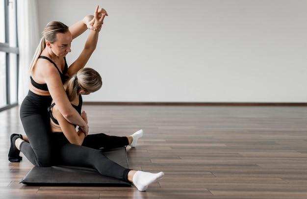 Vrouwelijke persoonlijke trainer en haar kopie ruimte van het zijaanzicht van de cliënt