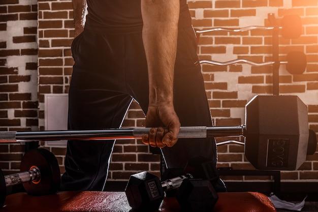 Vrouwelijke persoonlijke trainer helpt een jonge man dumbells op te heffen tijdens het trainen in een sportschool