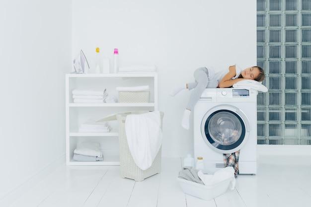 Vrouwelijke peuter slaapt op wasmachine, wordt moe met wassen, vormt in witte grote wasruimte met mand en bekken vol met vuile kleren flessen vloeibaar poeder. jeugd, huishoudelijke taken