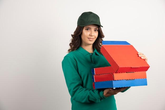 Vrouwelijke pizzakoerier die een geopende pizzadoos houdt.