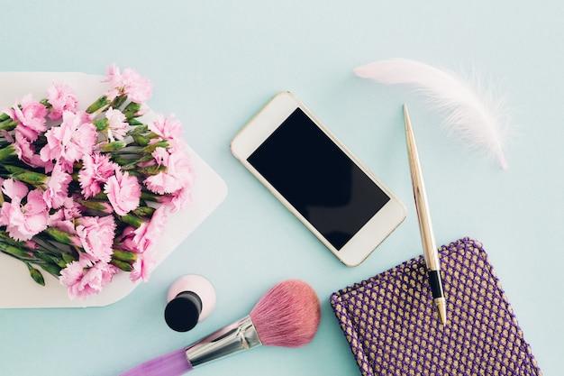 Vrouwelijke plat lag op blauw, bovenaanzicht van het bureaublad van de vrouw met envelop, bloemen, pen, notitieblok en smartphone. bespotten