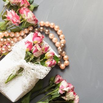 Vrouwelijke plat lag scène rozen bloemen, cadeau en ketting op grijs neutraal. bovenaanzicht.