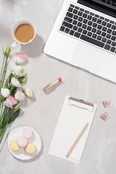 Vrouwelijke platliggende werkruimte met laptop, kopje thee, macarons, lippenstift en bloemen op witte tafel