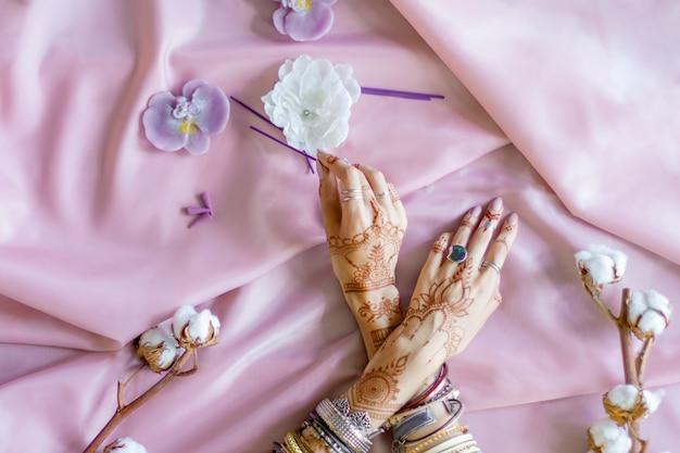 Vrouwelijke polsen beschilderd met traditionele indiase oosterse mehndi-ornamenten. handen gekleed in armbanden en ringen houden aromastick. roze stof met plooien, katoenen takken en kaarsen op de achtergrond.