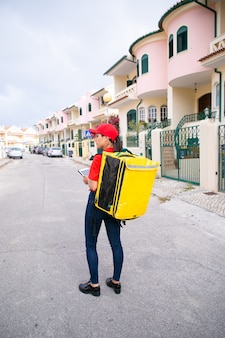 Vrouwelijke postbode in rood glb die zich met gele thermische zak bevindt en tablet vasthoudt. bezorger bezorgt te voet de bestelling.