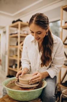 Vrouwelijke pottenbakker bij een aardewerkklasse