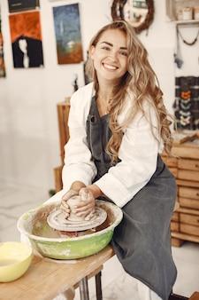 Vrouwelijke pottenbakker die met klei op wiel in studio werkt. klei met water spatte rond de pottenbakkersschijf.