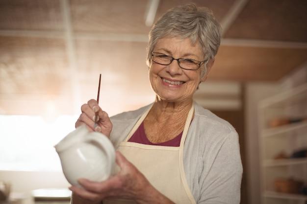 Vrouwelijke pottenbakker schilderen op kruik