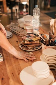 Vrouwelijke pottenbakkers die het ceramische palet op houten lijst schikken