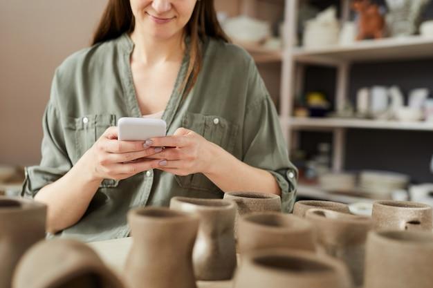 Vrouwelijke potter met behulp van smartphone