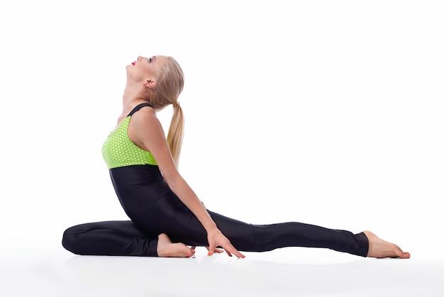 Vrouwelijke presterende yoga asana op wit wordt geïsoleerd