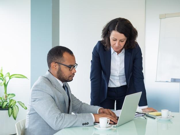 Vrouwelijke professional die nieuwe werknemer helpt