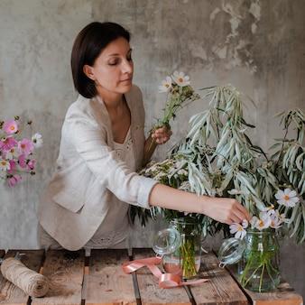 Vrouwelijke professionele bloemist bereidt de opstelling van wilde bloemen voor.