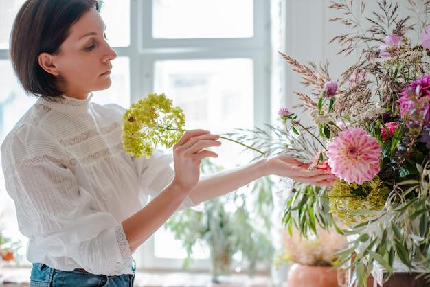 Vrouwelijke professionele bloemist bereidt de opstelling van wilde bloemen.