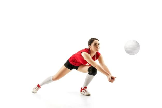 Vrouwelijke professionele volleyballspeler met bal die op witte studioachtergrond wordt geïsoleerd. de atleet, oefening, actie, sport, gezonde levensstijl, training, fitness concept. het meisje in beweging