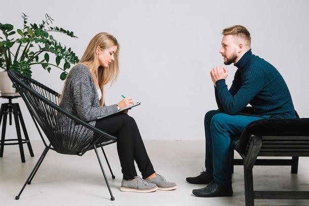 Vrouwelijke psycholoog die aan gedeprimeerde mannelijke patiënt luisteren en nota's over klembord neerschrijven