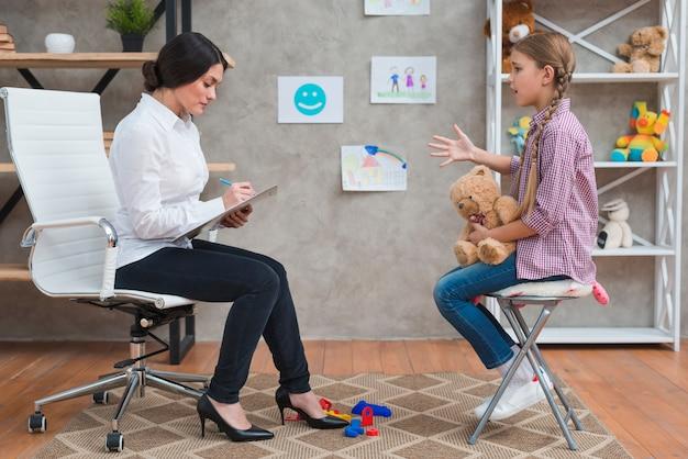 Vrouwelijke psycholoog die aantekeningen maakt tijdens therapie sessie
