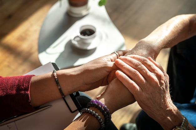Vrouwelijke psycholoog die de handen van een oudere patiënt vasthoudt