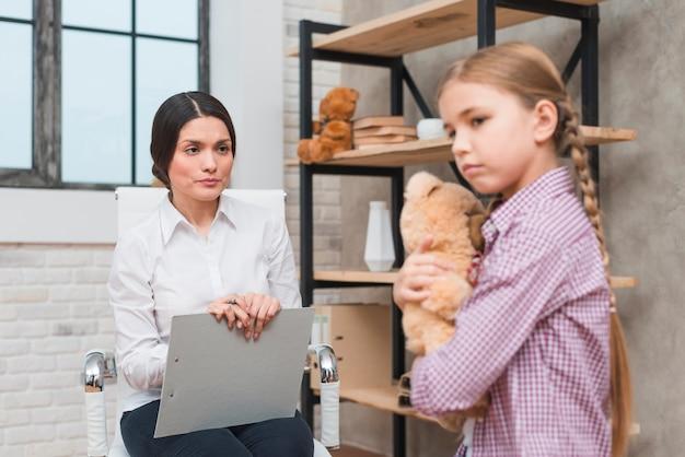 Vrouwelijke psycholoog die een therapiesessie met droevige teddybeer van de meisjesholding ter beschikking heeft