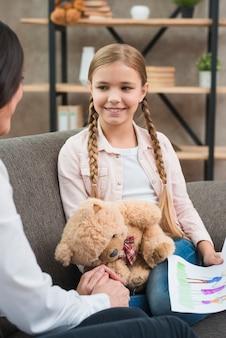 Vrouwelijke psycholoog die glimlachend meisje troosten tijdens therapiesessie