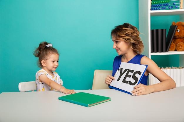 Vrouwelijke psycholoog die klein meisje in het kabinet adviseert.