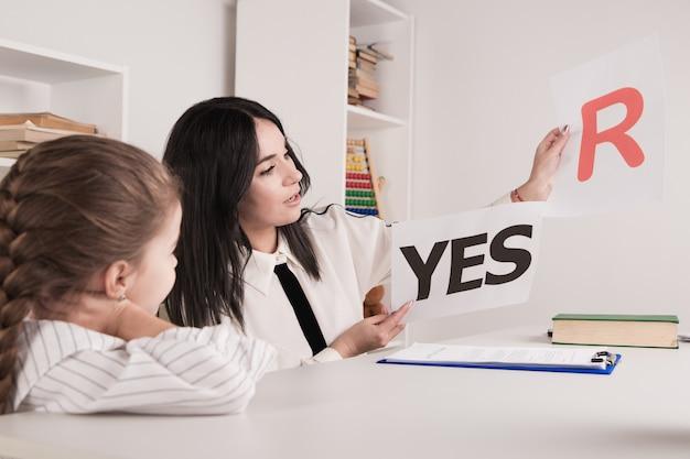 Vrouwelijke psycholoog die meisje in het kabinet adviseert.
