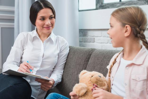 Vrouwelijke psycholoog die met de teddybeer van de meisjesholding tijdens therapiesessie spreekt
