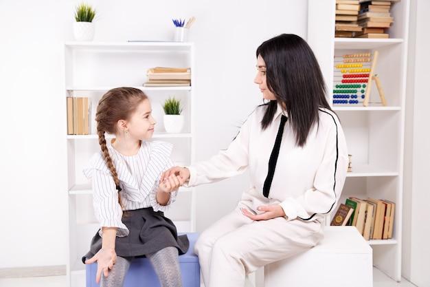 Vrouwelijke psycholoog die met meisje in de witte kast werkt.