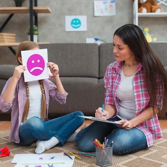 Vrouwelijke psycholoog die nota's nemen die meisje bekijken die haar gezicht behandelen met droevige emotiekaart