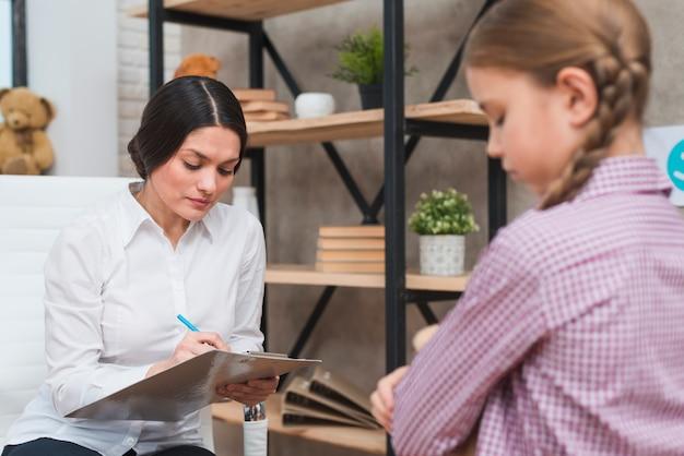 Vrouwelijke psycholoog die nota's over klembord nemen bij therapiesessie