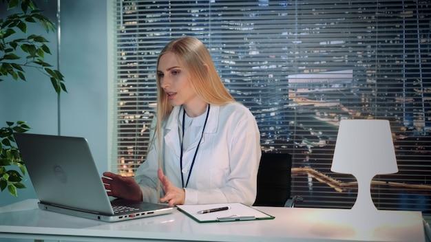 Vrouwelijke psycholoog in witte jas die online videoconsult met patiënt op computer maakt