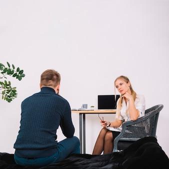 Vrouwelijke psycholoog serieus luisteren naar de patiënt op kantoor
