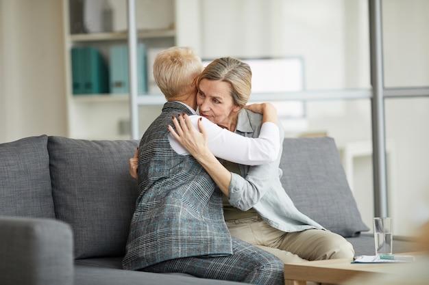 Vrouwelijke psycholoog troost volwassen vrouw in therapie sessie