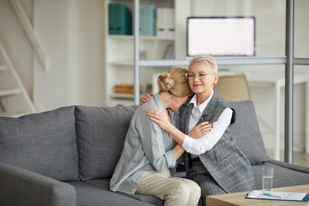 Vrouwelijke psycholoog troostende vrouw in therapie sessie