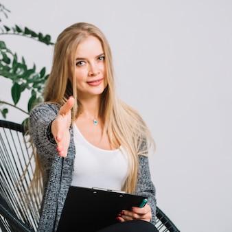 Vrouwelijke psycholoog zittend op een stoel verhogen haar hand voor schudden