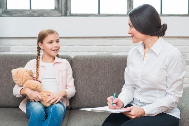 Vrouwelijke psycholoogzitting met de teddybeer die van de meisjesholding nota over klembord nemen