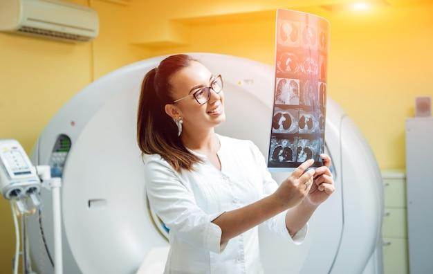 Vrouwelijke radioloog die röntgenstraal in de ruimte van computertomografie bekijkt.