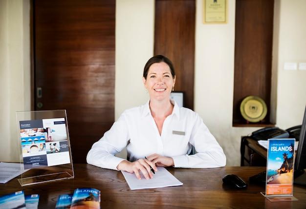 Vrouwelijke receptioniste die bij de receptie werkt