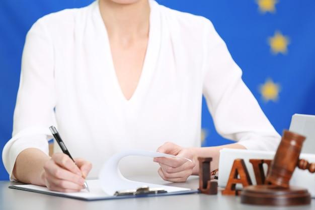 Vrouwelijke rechter die met documenten en wetstoebehoren op tafel werkt