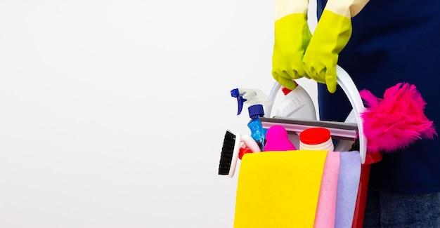 Vrouwelijke reiniger met een emmer met schoonmaakproducten. begrip schoonmaakservice.