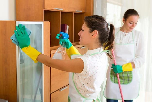 Vrouwelijke reinigingsmachines die ruimte schoonmaken