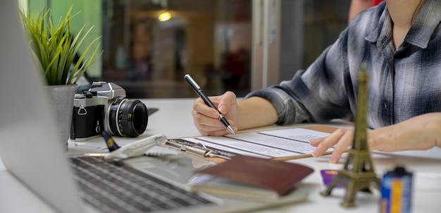 Vrouwelijke reis die met het vullen van het formulier van de reisverzekering voorbereidingen treft en informatie over laptop kijkt