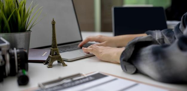 Vrouwelijke reis voorbereiden, informatie zoeken op leeg scherm laptop op witte tafel met reizen items
