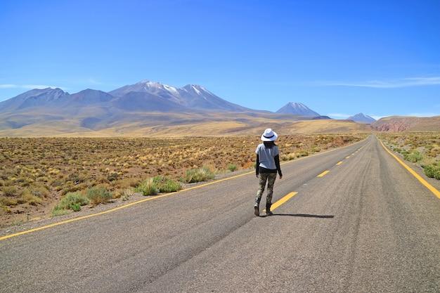 Vrouwelijke reiziger die alleen op de lege weg van atacama-woestijn in noordelijk chili loopt