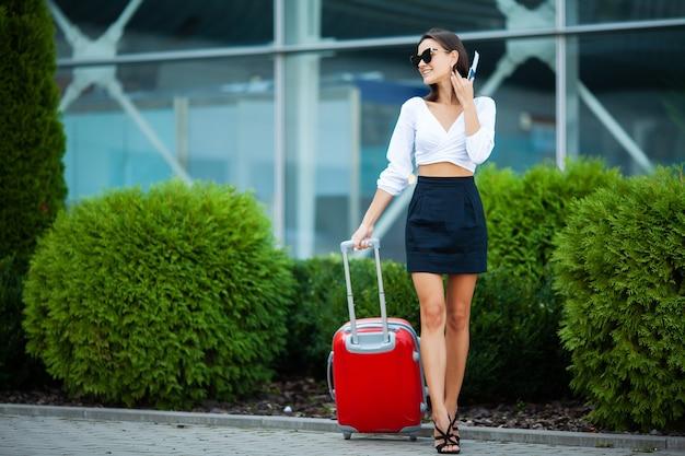 Vrouwelijke reiziger die met hun bagage dichtbij luchthaven loopt