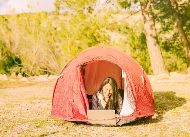 Vrouwelijke reiziger die met laptop in het kamperen werkt